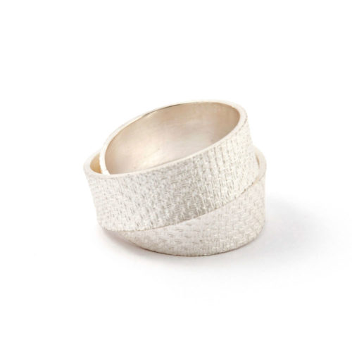 Minimalist ring of bleached silver with crosshatch imprint that wraps double around your finger.
