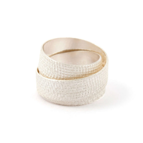 Silver wrapping ring of bleached silver with crosshatch imprint that wraps triple around your finger.