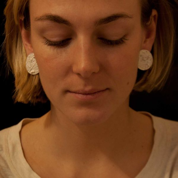 sophie wearring disc shaped casted silver earrings with an imprint of plants.